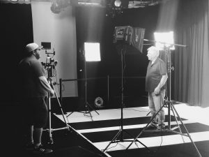 Image of 2 men in the Ignite Studio, surrounded by lights and cameras