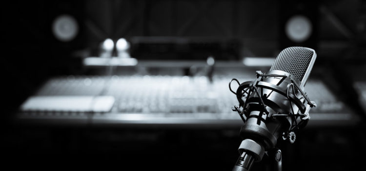 Black and white photo of a microphone in a recording studio